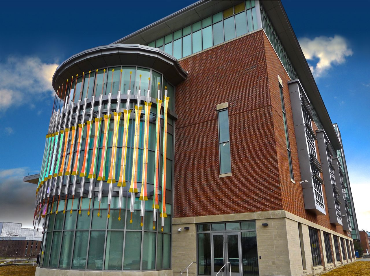 Rohrer College of Business at Rowan University exterior view of Threshold laminated dichroic glass and perforated stainless steel sculpture abstractly refers to gate imagery. / image 3