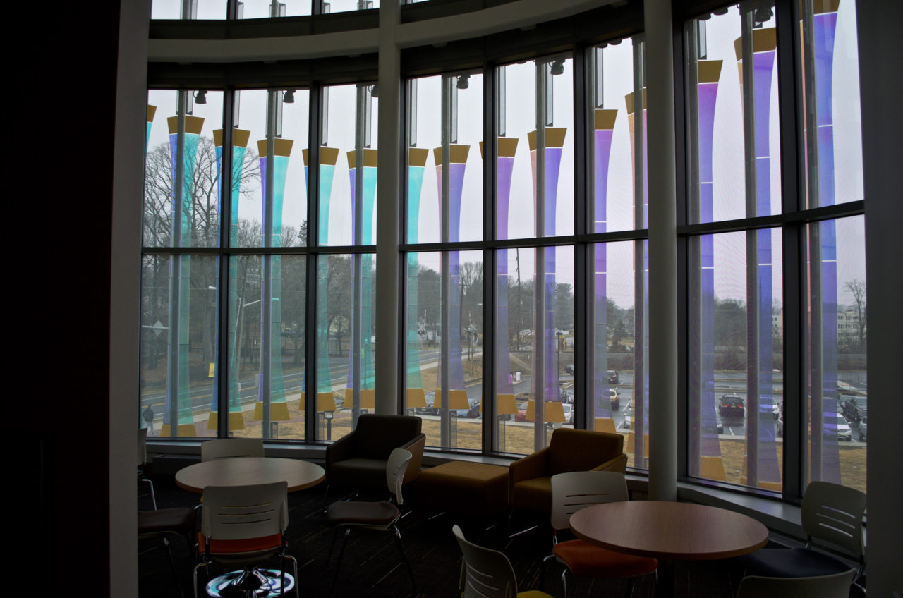 Rohrer College of Business at Rowan University interior view showing varying color views through Threshold laminated dichroic glass and perforated stainless steel sculpture. / image 7