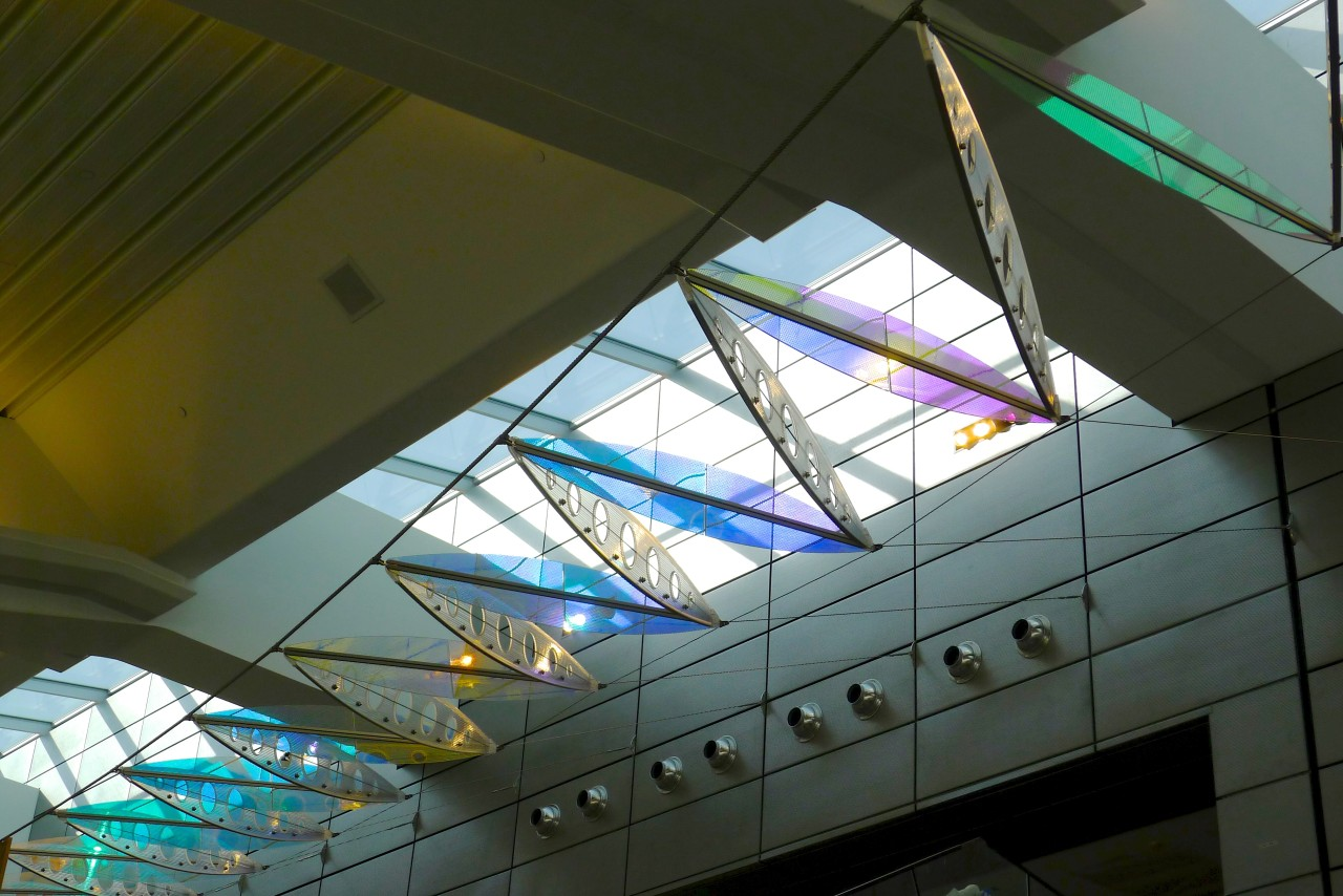 Ed Carpenter's Wichita Dwight D. Eisenhower National Airport signature sculpture Aloft delights travelers with colorful laminated safety dichroic glass above. / image 10