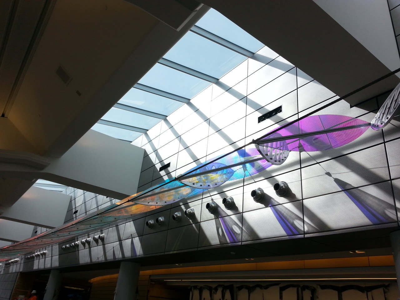 Ed Carpenter's Wichita Dwight D. Eisenhower National Airport signature sculpture Aloft delights travelers with colorful laminated safety dichroic glass above as well as producing ever changing color patterns on the walls. / image 11