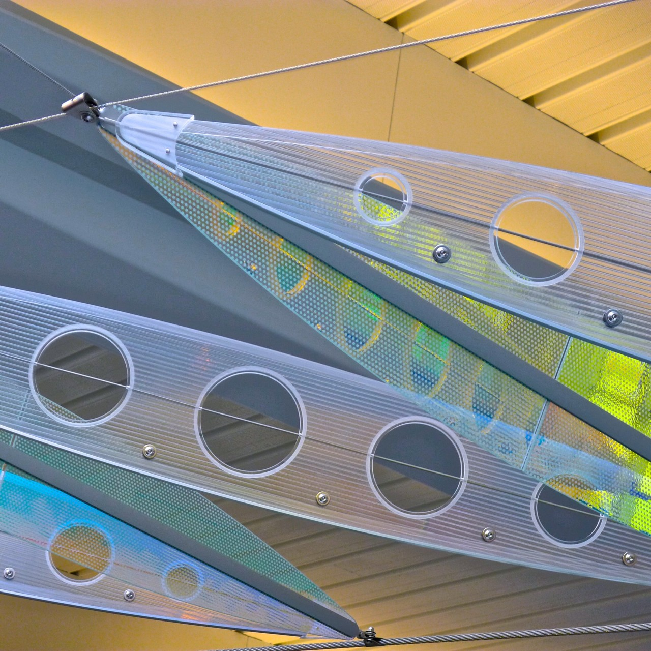 Showing Ed Carpenter's Wichita Dwight D. Eisenhower National Airport signature sculpture Aloft close up of alternating colorful laminated safety dichroic glass and cellular polycarbonate. / image 16