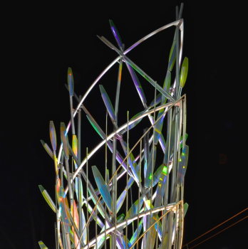 Ed Carpenter's Mesaflora sculpture in the core of the Country Club Road light rail station marks the western entry into downtown Mesa. The light rail station sculpture's up-lighting shown here in twilight and full night.