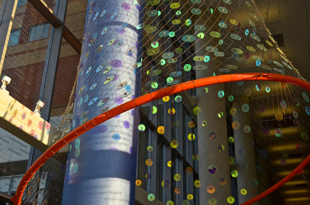 Ed Carpenter's Foxglove suspended glass art sculpture for San Antonio's new university's hospital lobby close up image of the stainless steel net and painted ring with jewels of dichroic glass. / image 2