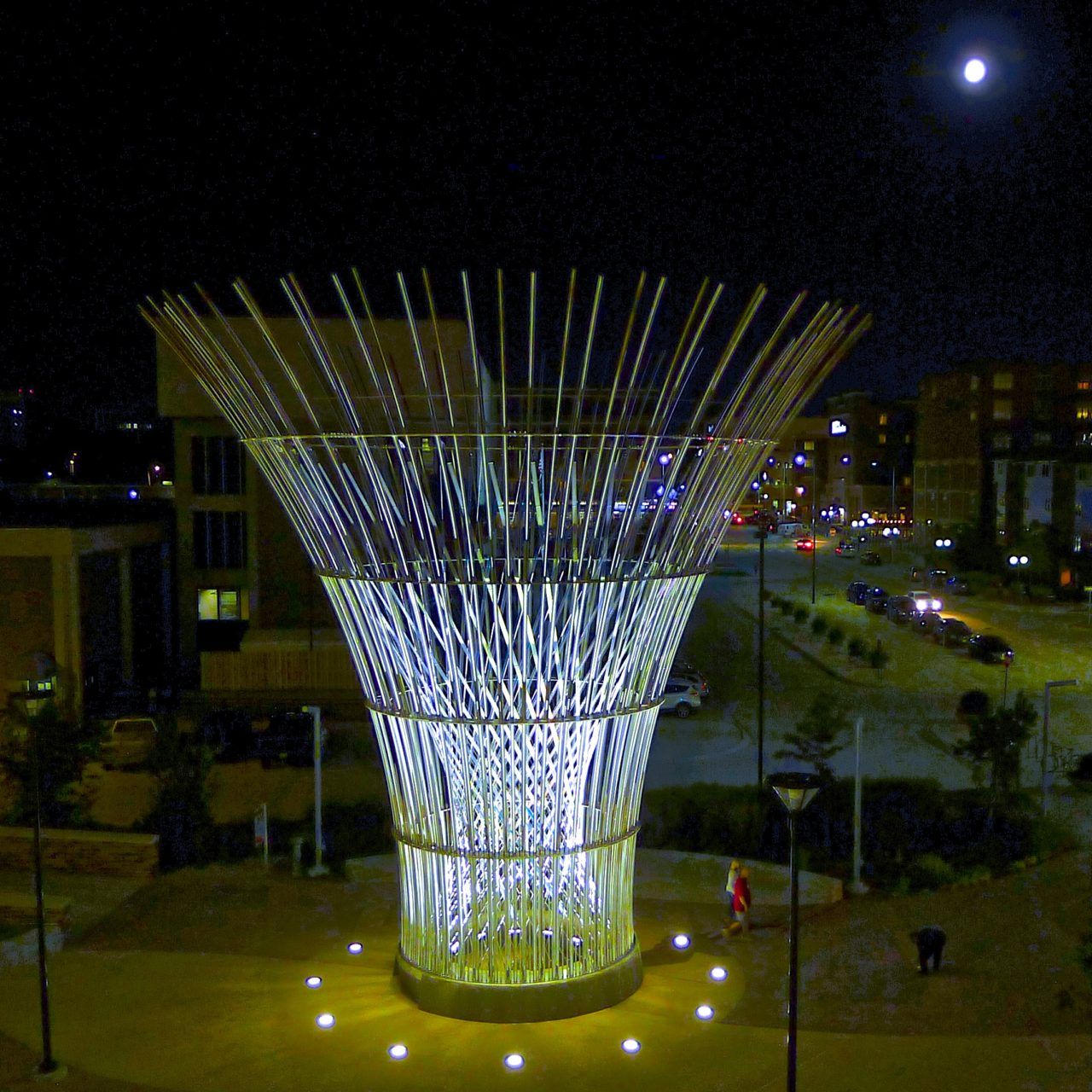 Harvest monumental public sculpture in Lincoln, Nebraska night lighting in the plaza in front of the Pinnacle Bank Arena amplifies the laminated dichroic glass elements crisscrossing in the center of the sculpture. / image 3