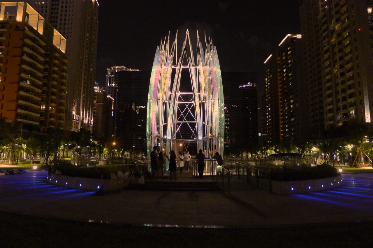 Night view shows carefully placed LED lighting dramatically illuminating the sculpture, Crocus. Taichung, Taiwan Civic Center monumental sculpture: Stainless Steel and Laminated Dichroic Glass / image 1