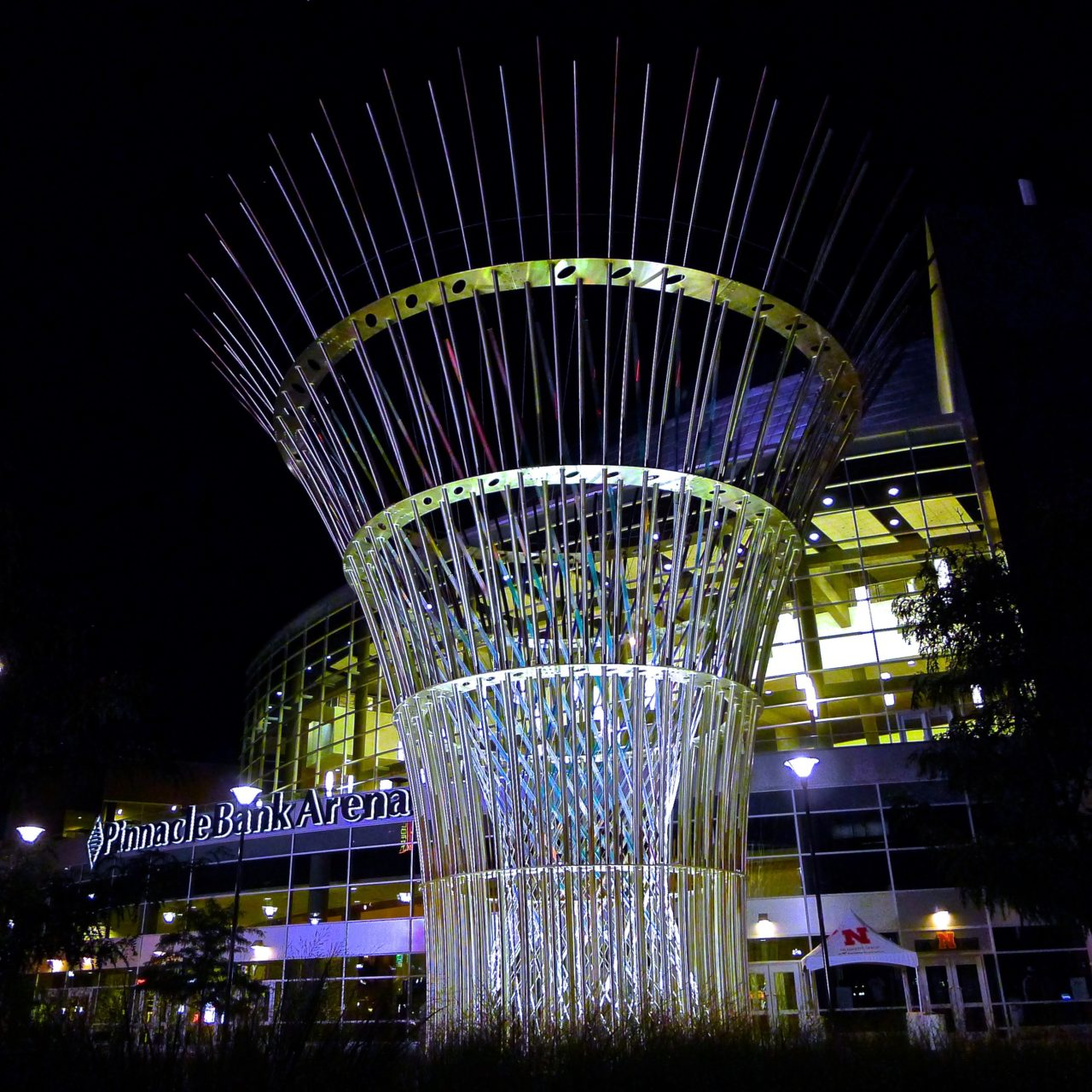 Harvest monumental public sculpture in Lincoln, Nebraska with night lighting in the plaza in front of the Pinnacle Bank Arena amplifies the stainless steel and dichroic glass structural tension elements crisscrossing in the center of the sculpture. / image 1