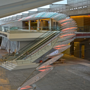 Ed Carpenter's Dwight D. Eisenhower National Airport sculpture Aloft in Wichita, Kansas, soars from one end of the building to the other like an enormous abstract wing. Here is an overall view of the lobby sculpture made of laminated dichroic safety glass, stainless steel cables and hardware, and cellular polycarbonate.